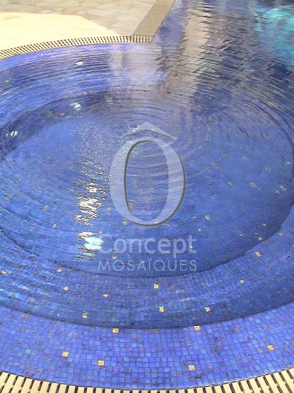 Un spa rond intégré dans la piscine en bleu indigo